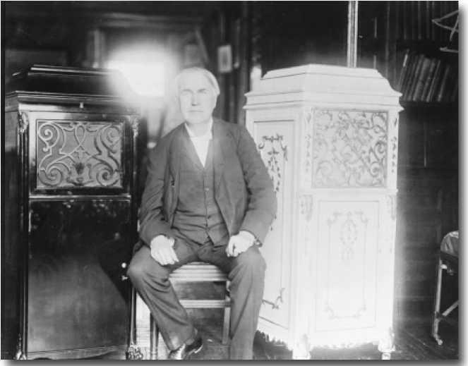 Эдисон сидит между двумя граммофонными ящиками (бетонный справа)